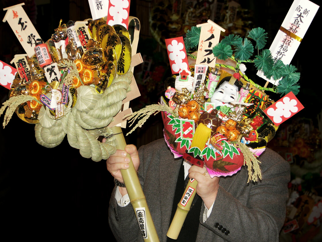 a salaryman holding Kumade (rake) in Hanazono shrine for tori no ichi festival